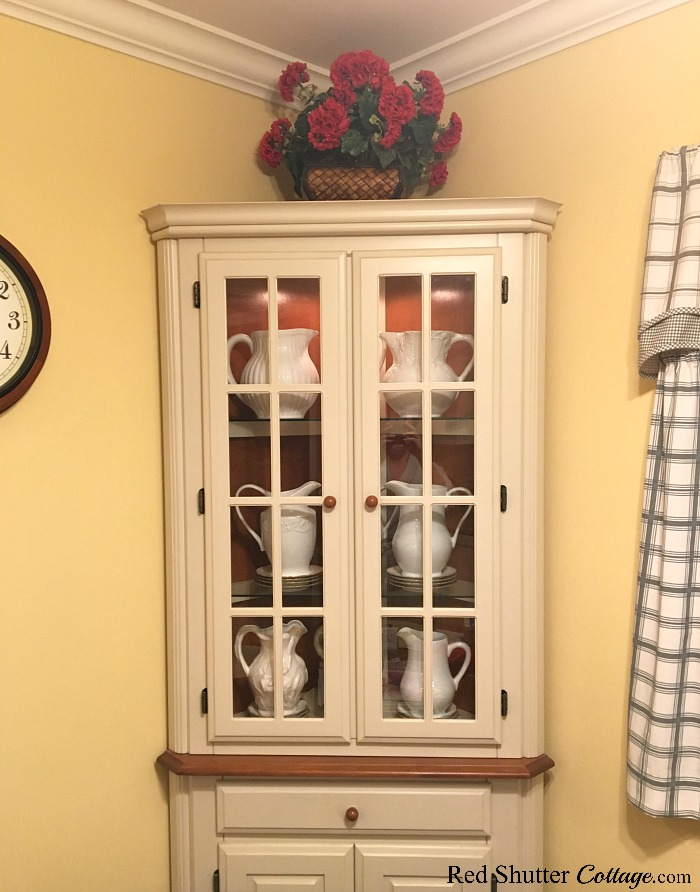 In this photo, the hutch doors are closed, but the pitchers are still clearly visible. This is one of the ideas I had for 3 Tips for Styling a Kitchen Hutch and Plate Shelf. www.redshuttercottage.com