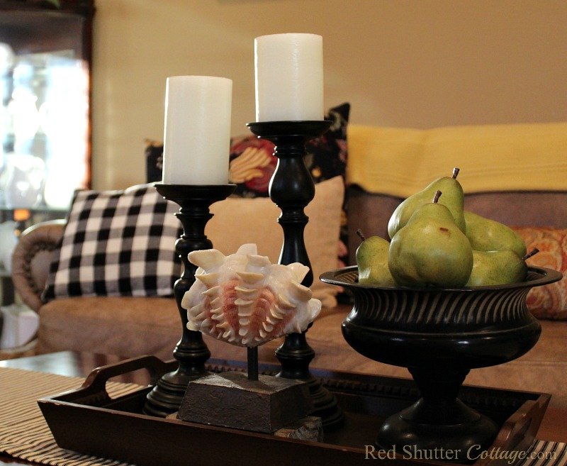 A simple vignette of candles, pears and a shell works well with buffalo check pillows in the living room. www.redshuttercottage.com