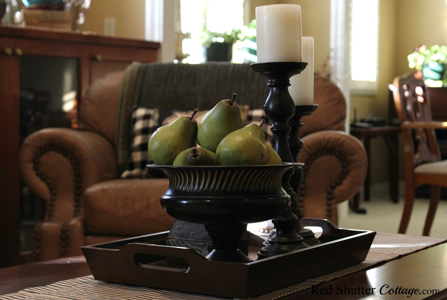 A bowl of pears with a couple of candleholders and candles are a complementary part of buffalo check pillows in the living room. www.redshuttercottage.com