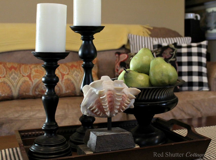 A table runner and pillow, both in pillow ticking stripes mix in perfectly with buffalo check pillows in the living room. www.redshuttercottage.com