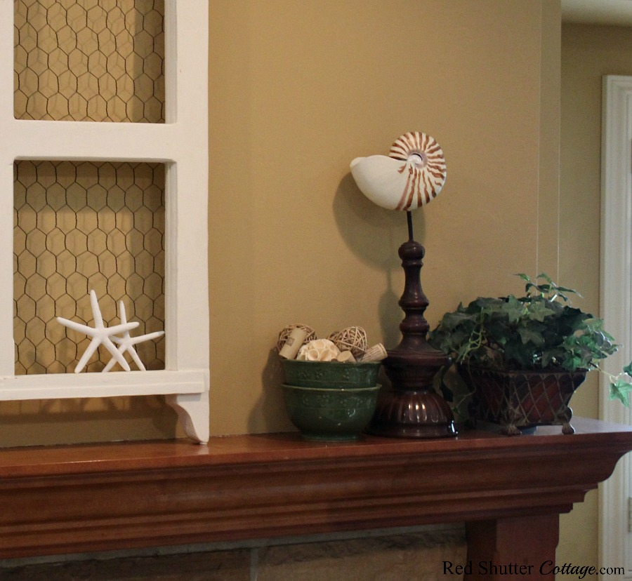 Shells, ivy and a bowl of twig balls create a neutral and easy mantel that fits right n with buffalo check pillows in the living room. www.redshuttercottage.com