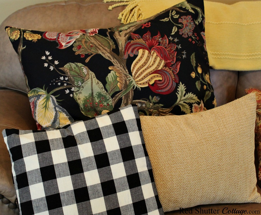 A trio of pillows on the couch in complementary colors are part of buffalo check pillows in the living room.