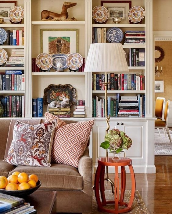 An image of a Traditional style room with bookcases, plates, fruit and flowers, part of How to Mix Up Your Decor Style. www.redshuttercottage.com