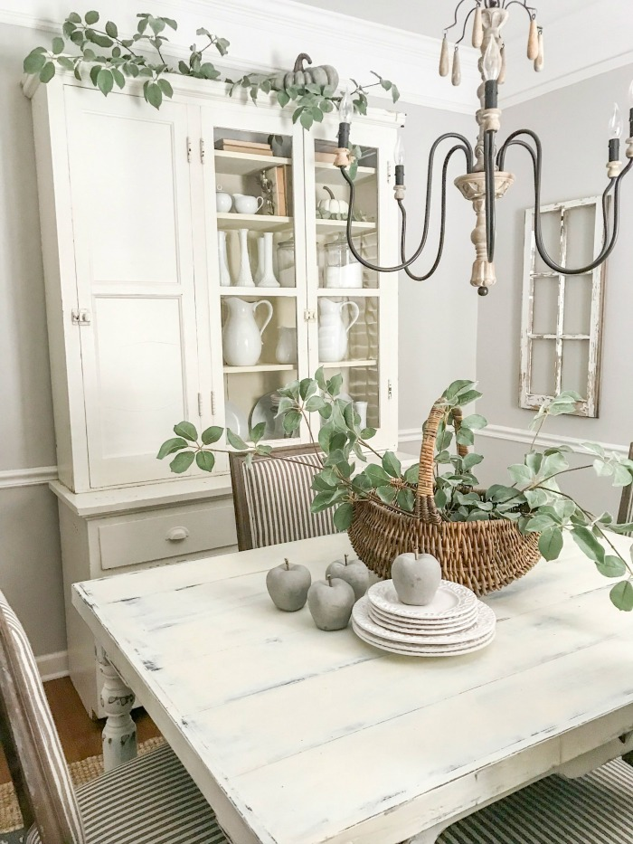 There is a fall feel to this farmhouse kitchen table, that includes a hutch and a chippy window frame. www.redshuttercottage.com