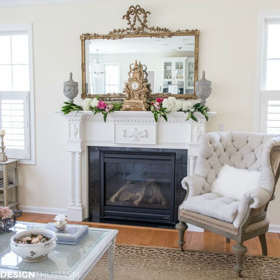This living room shows a French Country look, complete with a gilt-edged mirror, ornate clock, and chandeliers. This French Country style is part of How to Mix Up Your Design Style. www.redshuttercottage.com