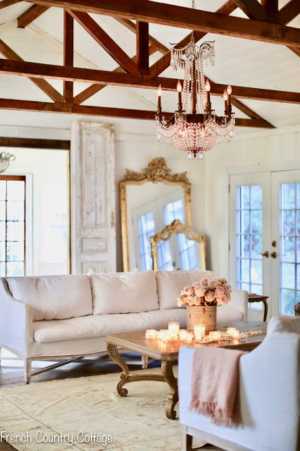 Complete with gilt-edged mirrors and a chandelier, this living room from French Country Cottage is both elegant and inviting. This is an example of French Country design as part of How to Mix Up Your Design Style. www.redshuttercottage.com