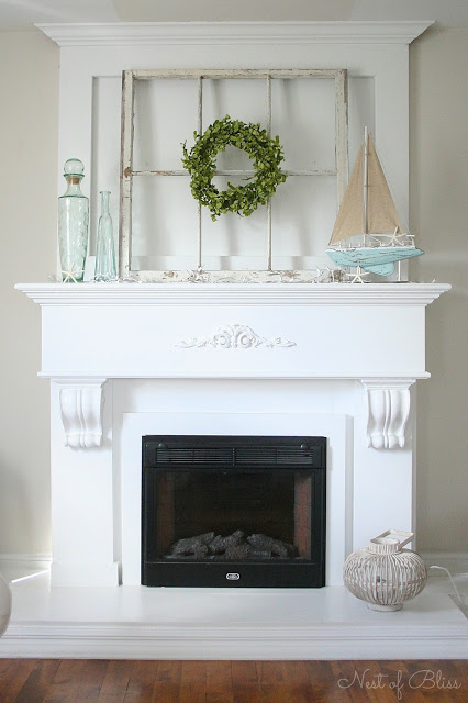 This mantel decorated with shells, sea glass bottles and a model sailboat is an example of Coastal Design, part of How to Mix Up Your Design Style. www.redshuttercottage.com