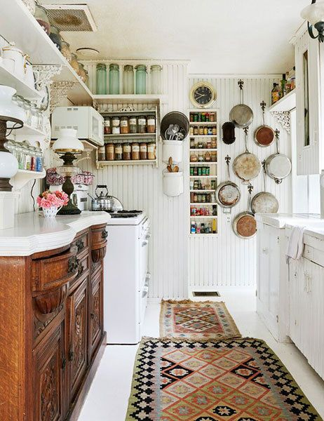 This kitchen cottage is anchored by a beautiful dresser, mixed in with beadboard walls and groupings of bottles, spices and pans, part of How to Mix Up Your Decor Style. www.redshuttercottage.com