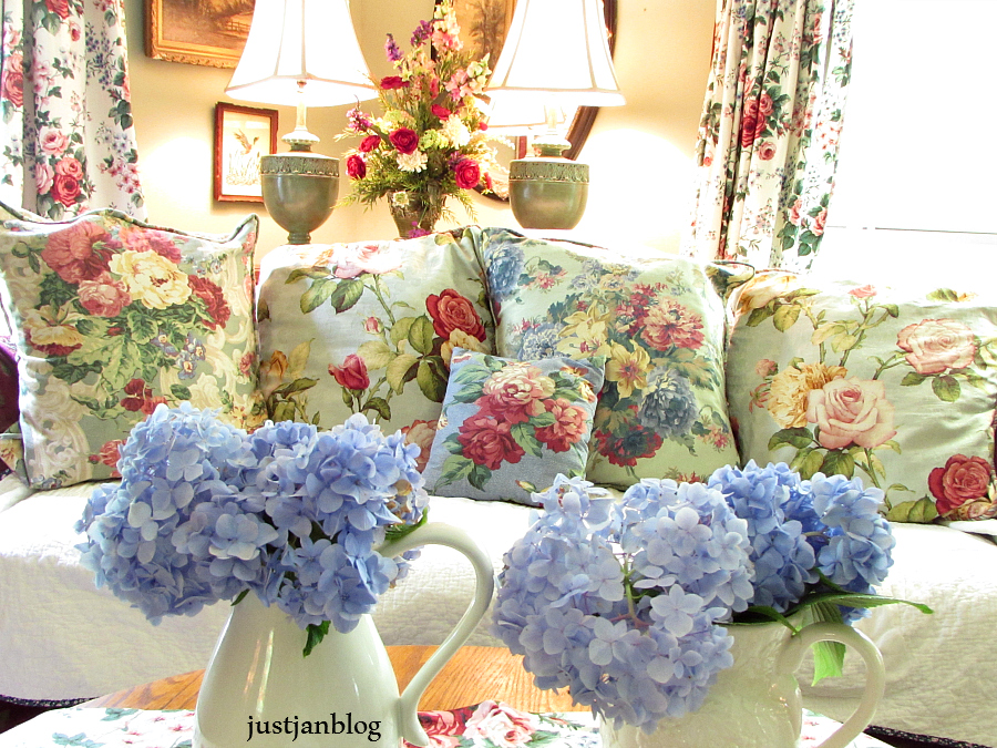 A bright, floral cozy living room as an example of cottage style, part of How To Mix Up Your Decor Style. www.redshuttercottage.com