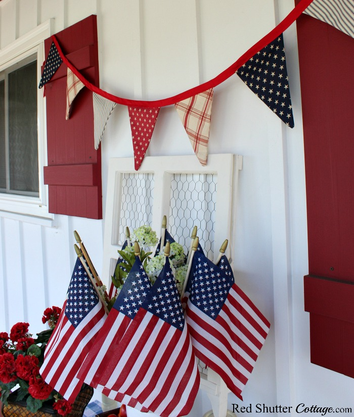 A festive 4th of July On The Front Porch includes a banner, flats, and hydrangeas and geraniums.