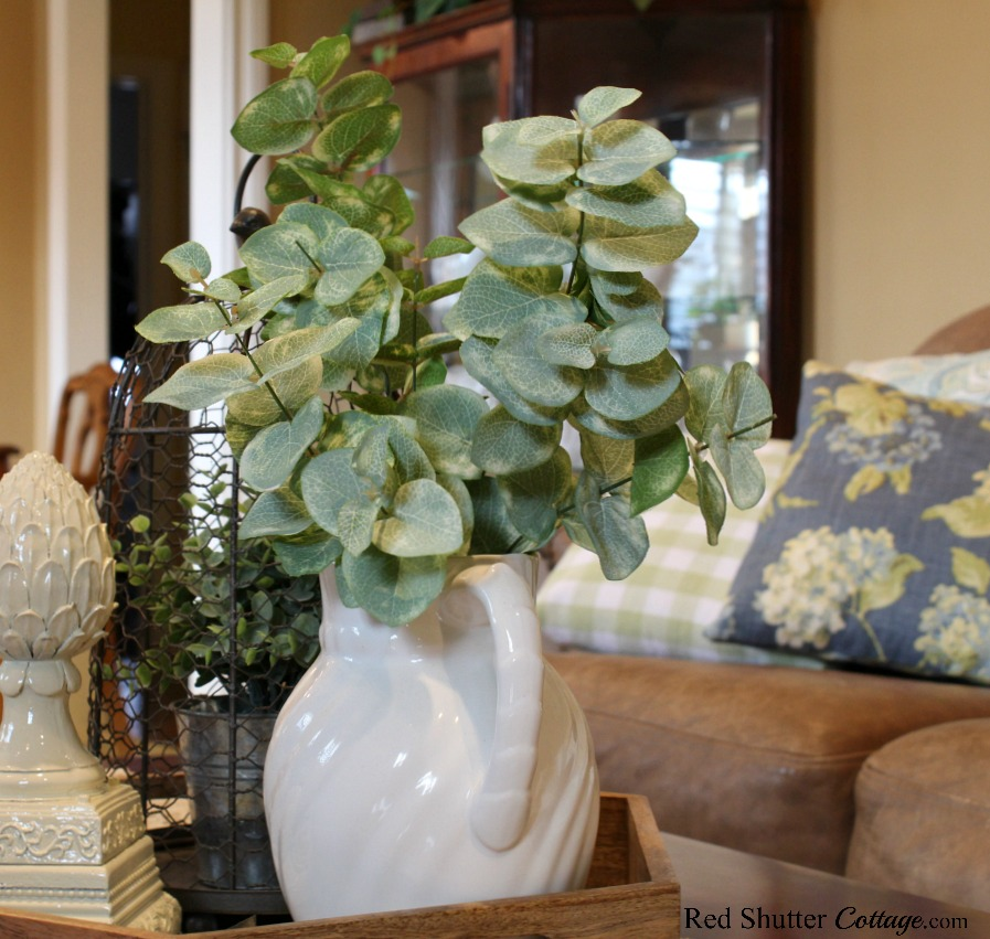 On the coffee table, a Laura Ashley pitcher full of greenery and a finial are part of Hydrangeas in the Summer Living Room. www.redshuttercottage.com