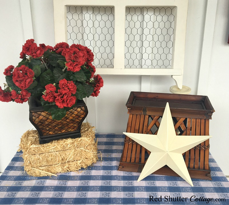 Geraniums on top of the bale of hay bring a pop of red to 4th of July On The Front Porch.