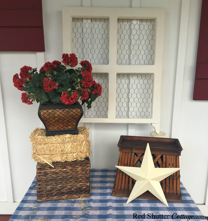Adding a basket underneath the bale of hay helps lift the red geraniums higher. All part of 4th of July On The Front Porch.