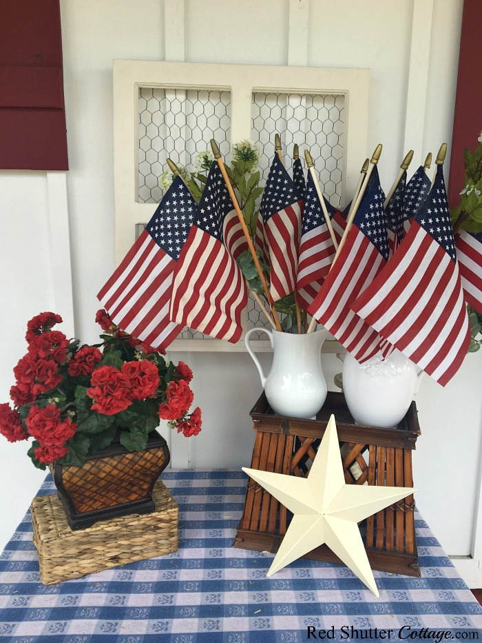 Lowering the geraniums helps create varying heights for 4th of July On The Front Porch.