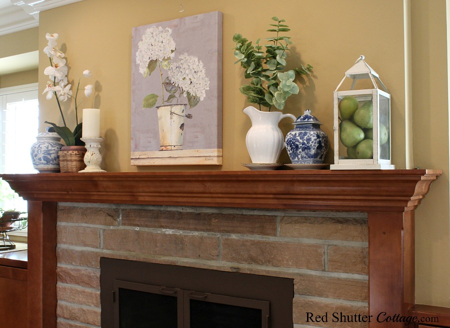 The mantel with light touches of greens, blues, and whites is a part of Hydrangeas in the Summer Living Room. www.redshuttercottage.com