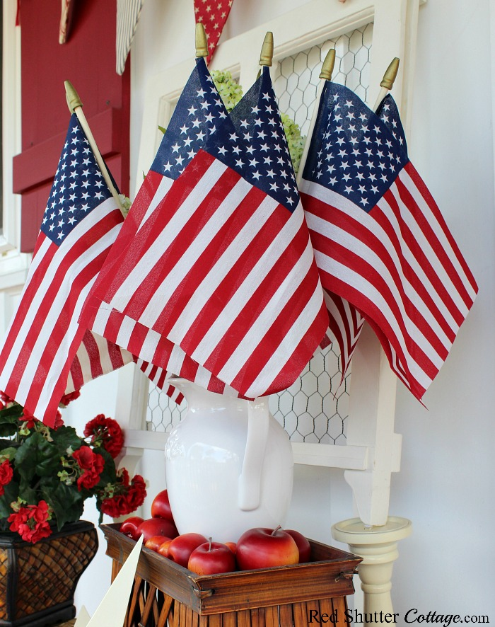A grouping of flags mixed in with hydrangeas is part of 4th of July On The Front Porch.