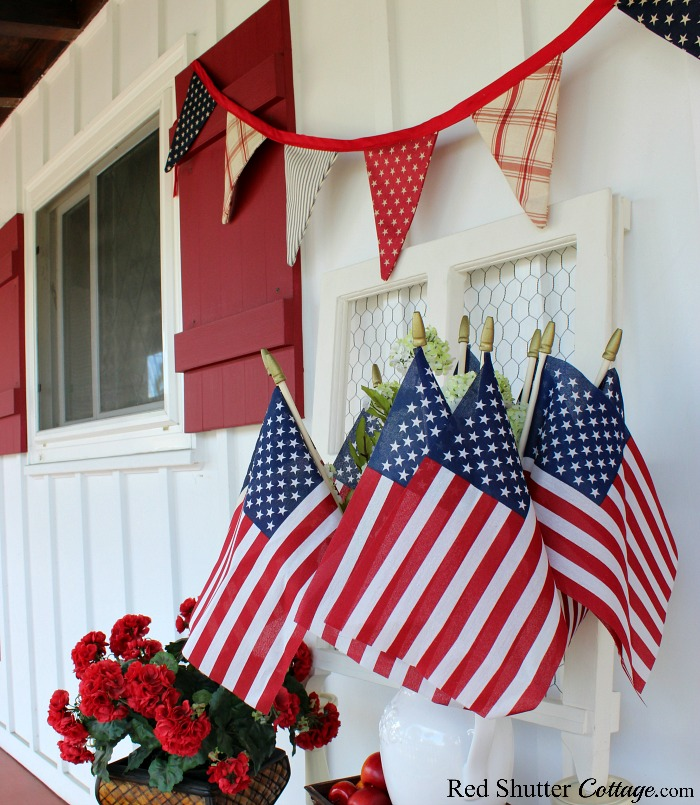 Stars and stripes in both the banner and the flags are part of 4th of July On The Front Porch.