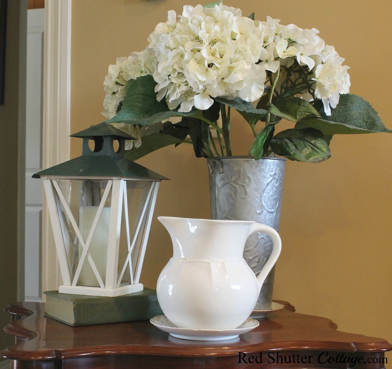 A simple vignette of hydrangeas, a lantern and a pitcher, all garage sale finds. This vignette is part of Hydrangeas in the Summer Living Room. www.redshuttercottage.com