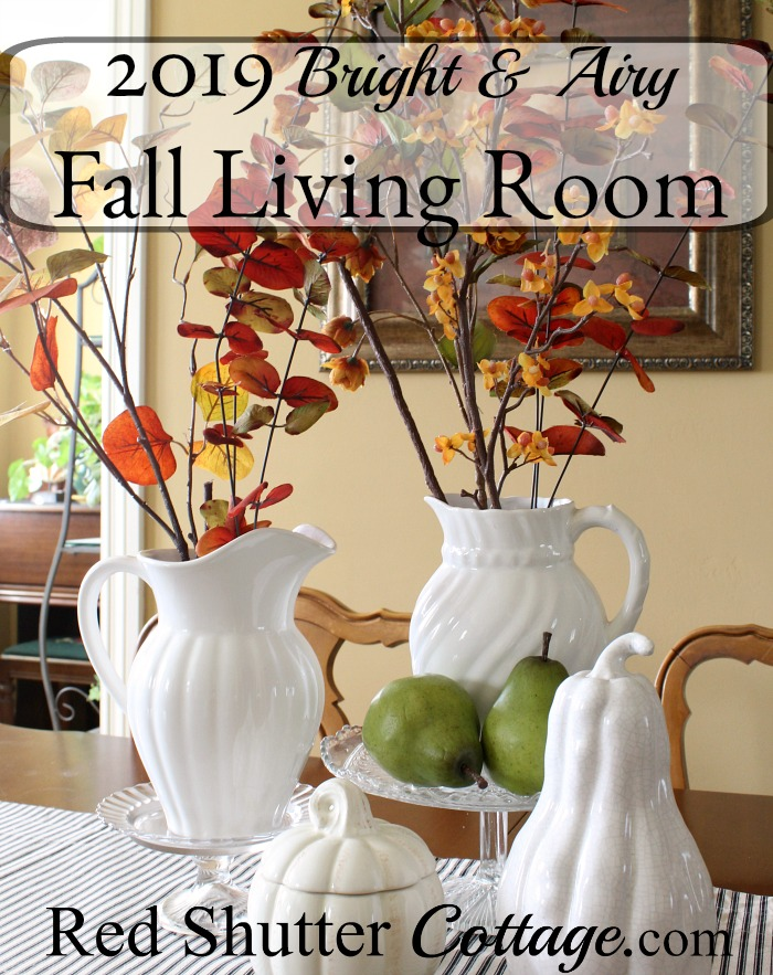 Fall display of white pitchers and foliage on dining table.