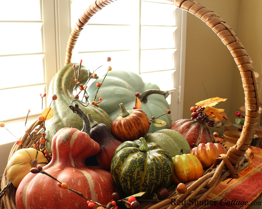A flower picking basket filled with fall fruit and berries on a fall plaid runner. All part of the 2019 Bright & Air Fall Living Room. www.redshuttercottage.com