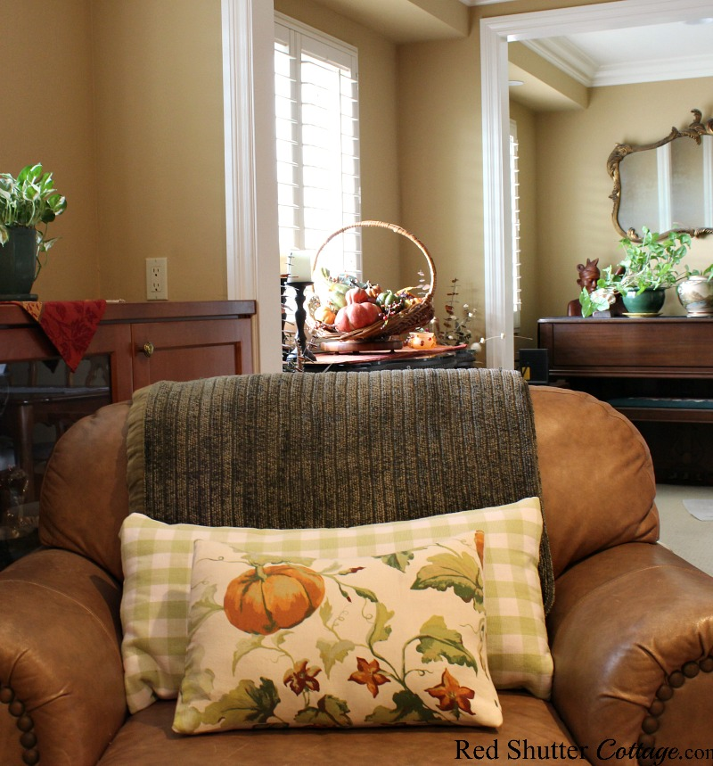 A long view of the dining room nook with a flower picking basket filled with fall fruit. www.redshuttercottage.com