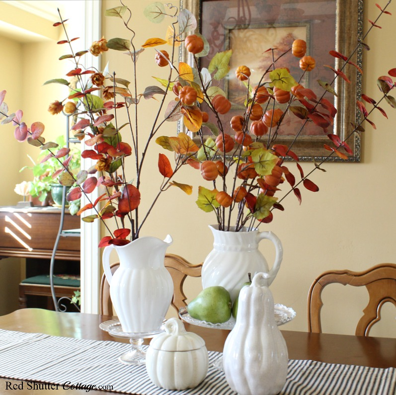 A display of warm and bright fall colors using white pitchers and fall branches to create the 2019 Bright & Airy Fall Living Room. www.redshuttercottage.com