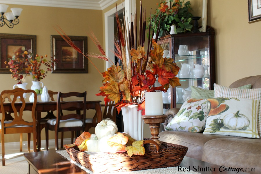 A wicker basket filled with fall pumpkins, wheat and autumn colored foliage is part of the 2019 Airy & Bright Fall Living Room. www.redshuttercottage.com