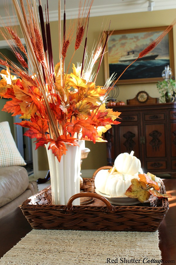 A vase of autumn leaves and a bowl of pumpkins are glowing with light from the late afternoon sun. All part of the 2019 Bright & Airy Fall Living Room. www.redshuttercottage.com