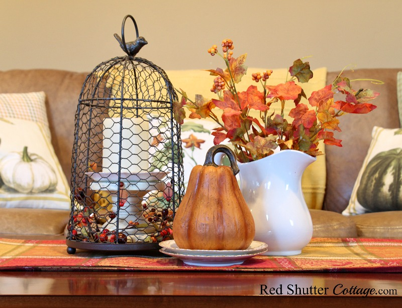 Pumpkins on pillows and a pumpkin on the coffee table are part of A Fall Coffee Table - 3 Ways. www.redshuttercottage.com