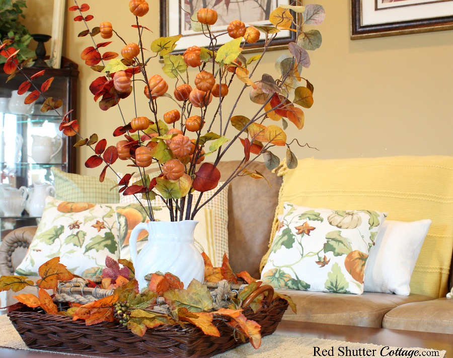 Fall pillows behind a white pitcher filled with fall branches, all part of A Fall Coffee Table - 3 Ways. www.redshuttercottage.com