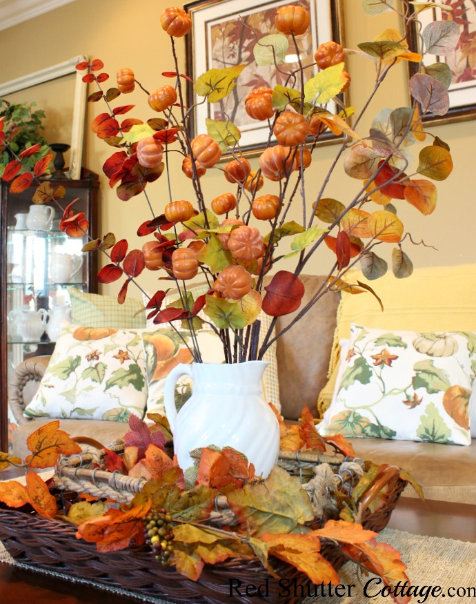 A combination of fall branches in a white pitcher and fall leaves in the baskets are part of A Fall Coffee Table - 3 Ways. www.redshuttercottage.com