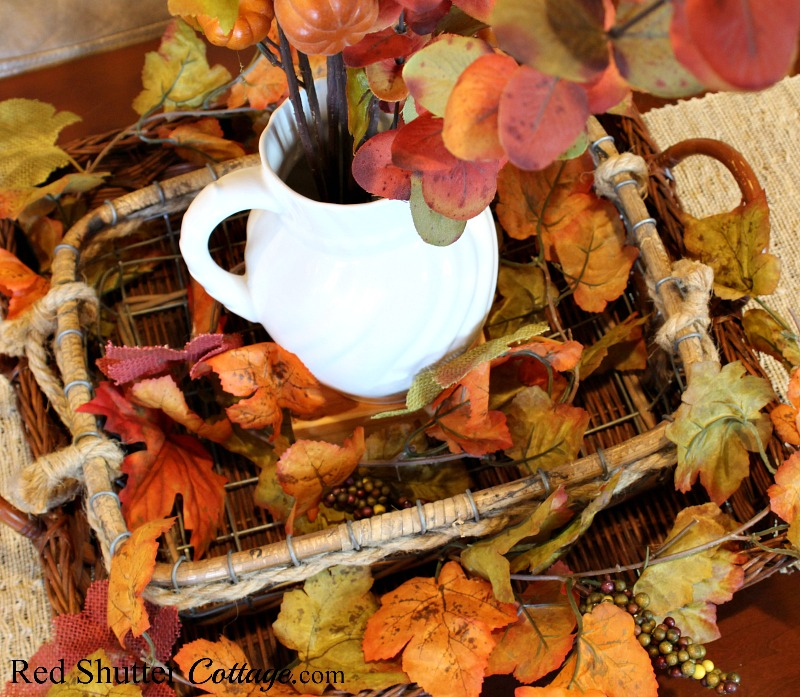 A downward view of two nested baskets filled with fall foliage and a white pitcher. All part of A Fall Coffee Table - 3 Ways. www.redshuttercottage.com