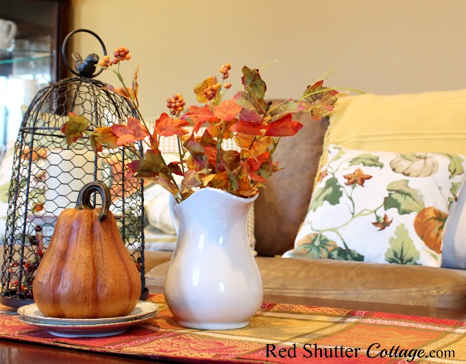 A variety of autumn colors in a runner, pillows and vignette are part of A Fall Coffee Table - 3 Ways. www.redshuttercottage.com