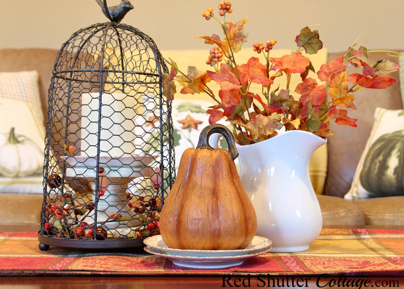 A cloche filled with a candle and bittersweet, along with a white pitcher filled with autumn leaves is one of the options in A Fall Coffee Table-3 Ways. www.redshuttercottage.com