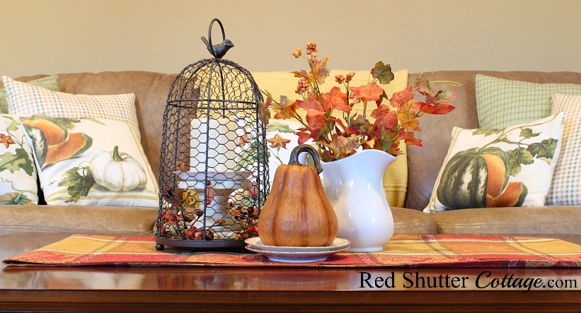 A coffee table adorned with a cloche, a pitcher of leaves and a pumpkin are all part of A Fall Coffee Table - 3 Ways. www.redshuttercottage.com