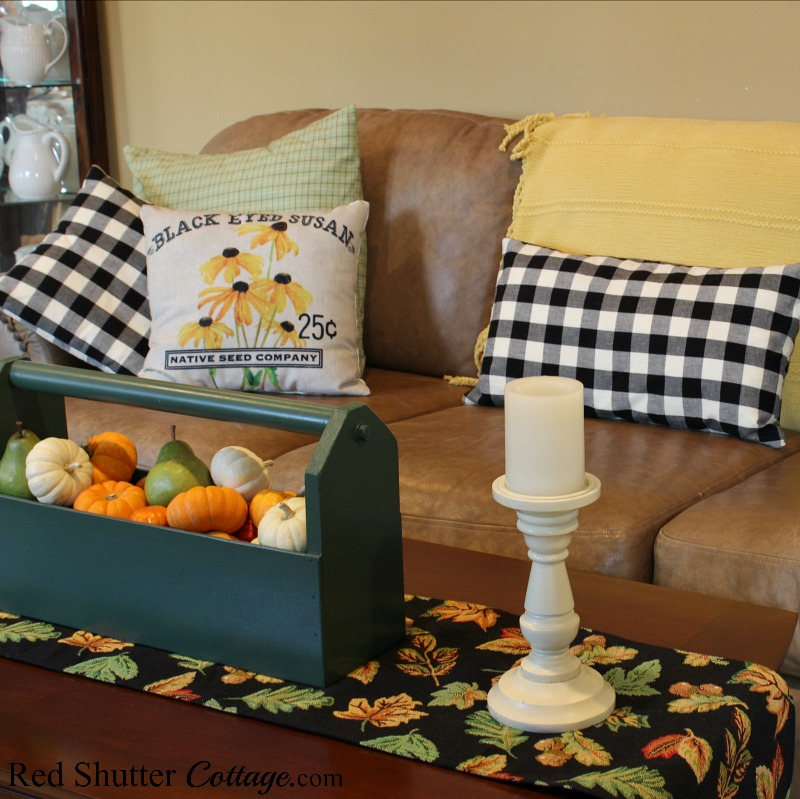 A table runner of fall leaves on a black background fits perfectly with buffalo check pillows and a tote filled with pumpkins, all part of A Fall Coffee Table - 3-Ways. www.redshuttercottage.com