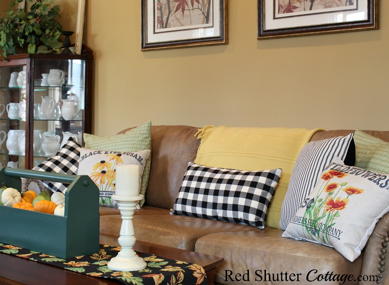 Buffalo check and seed packet-style pillows fit in naturally with a wooden tote filled with pumpkins, part of A Fall Coffee Table - 3 Ways. www.redshuttercottage.com