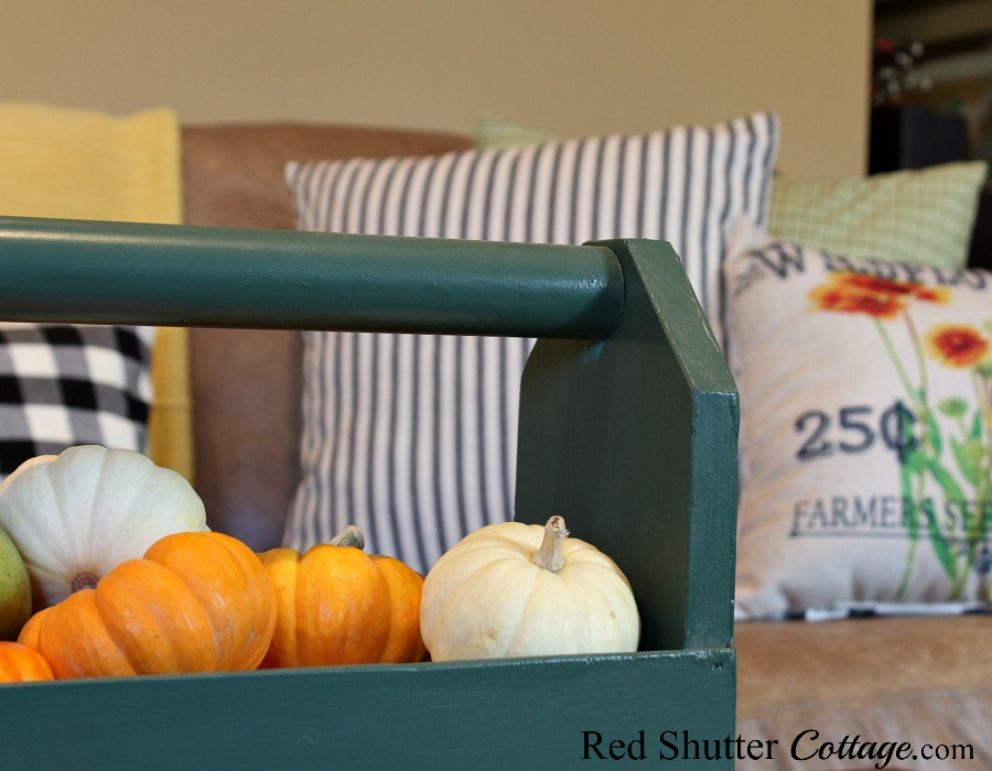 A wooden tote filled with fall fruit fits in with seed packet style pillows. All part of a Fall Coffee Table - 3 Ways. www.redshuttercottage.com