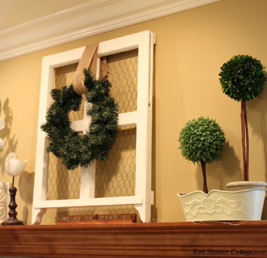 The mantle for an Early Winter Living room is lightly accessorized with neutral ivory and greens. www.redshuttercottage.com
