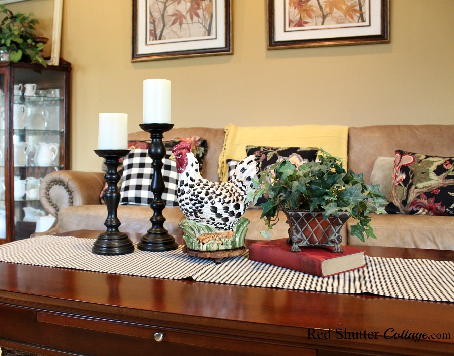 This ceramic rooster is right at home amidst candleholders, an ivy plant and pillow ticking runner, all part of Early Winter Living Room. www.redshuttercottage.com