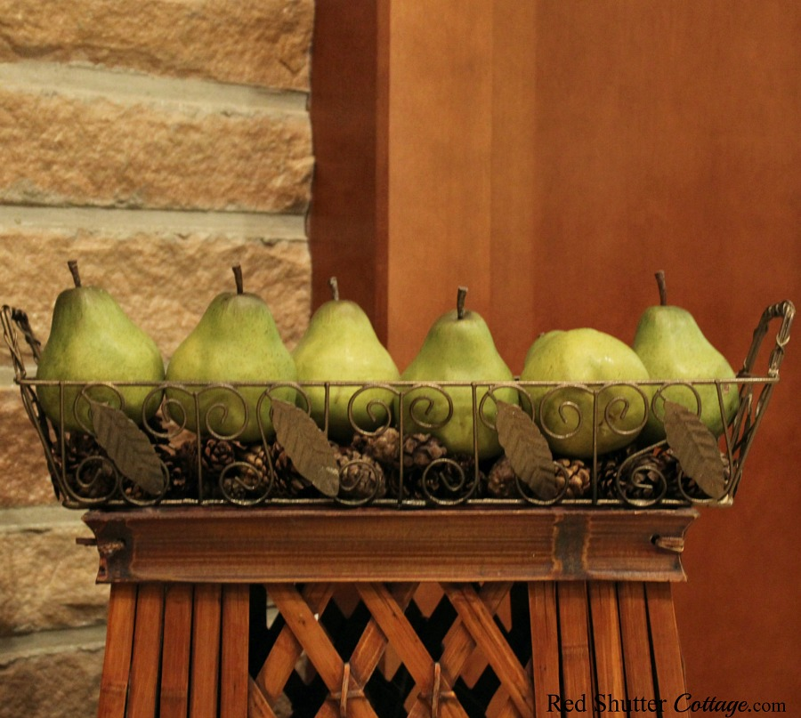 Pottery Barn pears, nestled in a thrift shop basket, atop a garage sale magazine holder, all part of the Early Winter Living Room. www.redshuttercottage.com