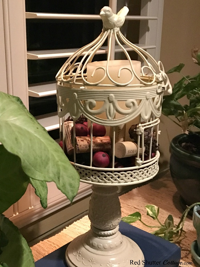 A petite bird cage with a new paint color, containing berries, wine corks and a candle.A great example of The Joy of Treasure Finds by Thrift Shopping. www.redshuttercottage.com