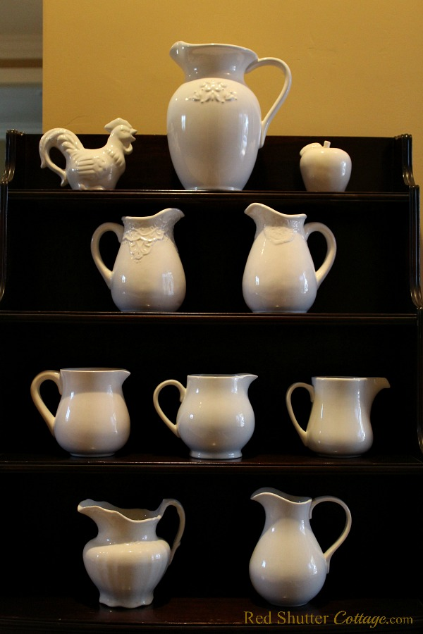 One part of my white pitcher collection, decorating my Grandmother's mahogany shelf unit. Some of these garage sale and estate sale finds. Another example of The Joy of Treasure Finds by Thrift Shopping. www.redshuttercottage.com