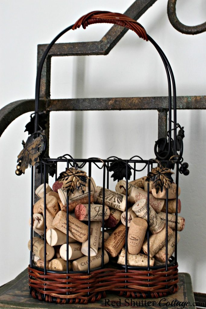 A wine bottle basket, repurposed to hold wine bottle corks. A great example of The Joy of Treasure Finds by Thrift Shopping. www.redshuttercottage.com