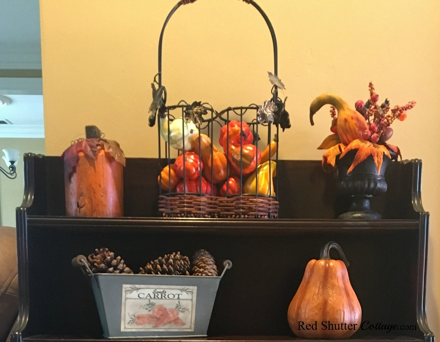 A wine bottle basket, re-purposed to hold miniature fall fruit.A great example of The Joy of Treasure Finds by Thrift Shopping. www.redshuttercottage.com