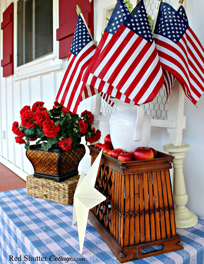 For this 4th of July display, I used a garage sale blue & white tablecloth, and a garage sale pitcher surrounded by rummage sale apples. Another example of 7 Tip for Successful Thrift Shopping. www.redshuttercottage.com