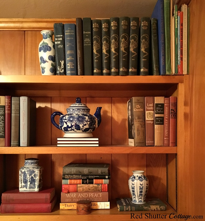 A small display of thrift shop blue & white porcelain filling the bookshelves in our TV room.A great example of The Joy of Treasure Finds by Thrift Shopping. www.redshuttercottage.com