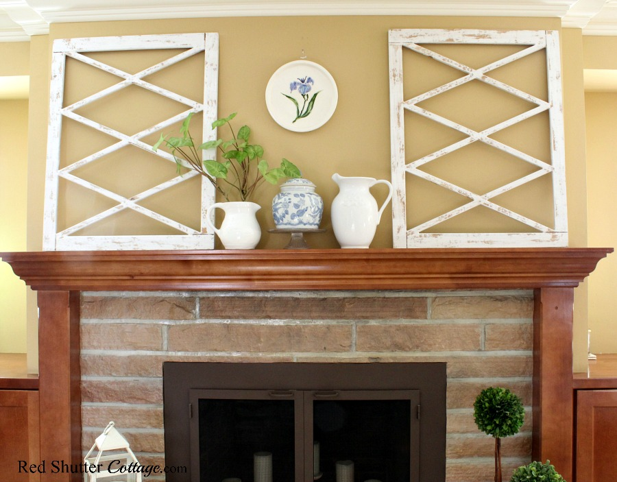 The mantel in a springtime living room is decorated with white pitchers and white architectural squares. www.redshuttercottage.com