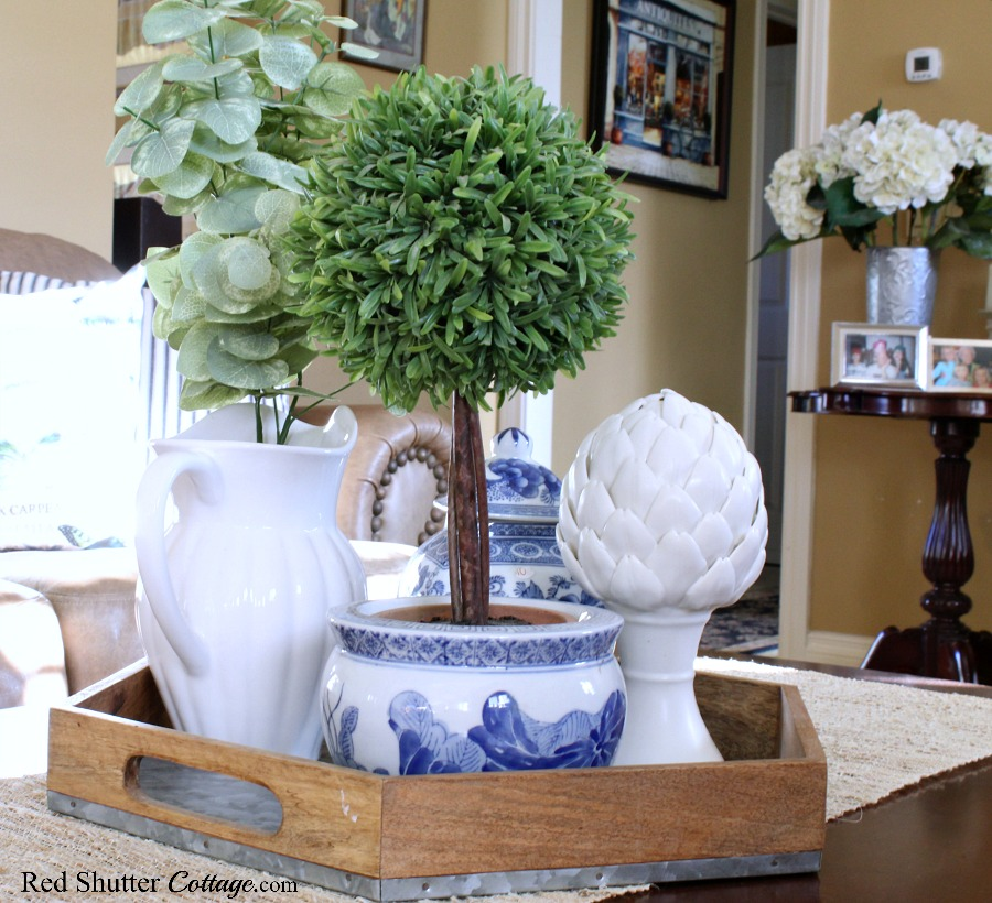 Blue and white pottery and topiary fill a coffee table tray in my springtime living room. www.redshuttercottage.com