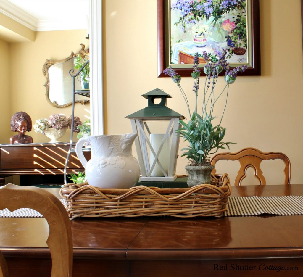 A thrift shop basket holds a pitcher, lantern and lavendar topiary in a springtime living room. www.redshuttercottage.com